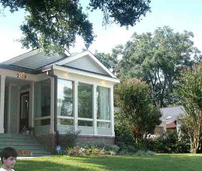East-Hill:-2109-Whaley-Drive_04.jpg:  glassed-in porch, front steps, lawn, oak tree, ranch-style home, crepe myrtle tree