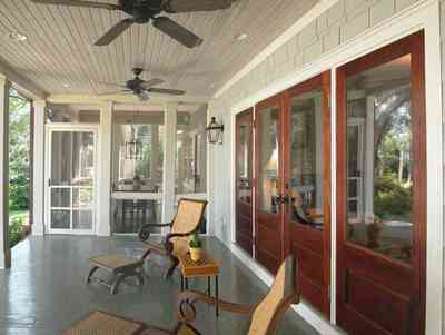 East-Hill:-2109-Whaley-Drive_09.jpg:  ceiling fan, beaded wooden ceiling, screen porch, wicker chairs, bayou view