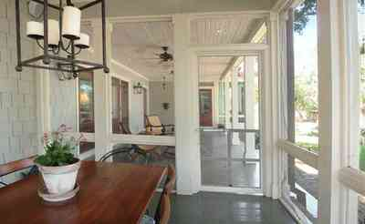 East-Hill:-2109-Whaley-Drive_14.jpg:  dining table, screen porch, wrought-iron lantern, wood shingles, ceiling fan, front porch