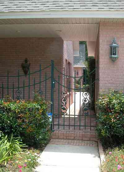 East-Hill:-617-19th-Avenue_09.jpg:  wrought-iron gate, pink brick house, side entrance