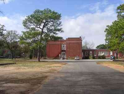 East-Hill:-Agnes-MacReynolds-School_04.jpg:  brick school house, parking lot, pine trees