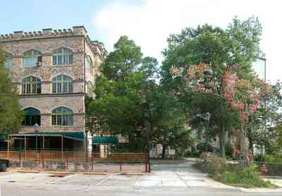 East-Hill:-Tower-East:-Old-Sacred-Heart-Hospital_20.jpg:  crepe myrtle tree, awning, wrought iron fence, pation fir tree, stone facade, battlement, stone courses
