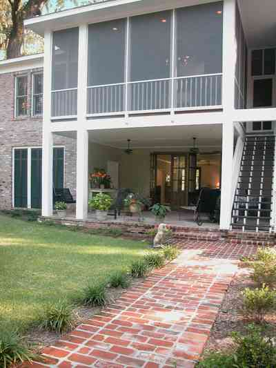 East-Pensacola-Heights:-112-Chipley-Avenue_21.jpg:  brick sidewalk, rear staircase, patio, veranda, shutters, brick facade, screen porch, columns