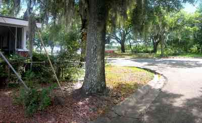 East-Pensacola-Heights:-118-Bayou-Blvd_04.jpg:  craftsman cottage, spanish moss, bayou texar, oak tree, red brick house
