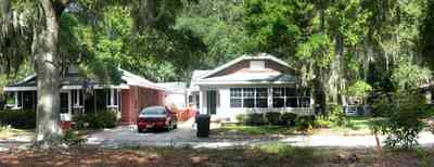 East-Pensacola-Heights:-118-Bayou-Blvd_06.jpg:  craftsman cottage, spanish moss, bayou texar, oak tree, red brick house