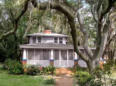 East-Pensacola-Heights:-600-Bayou-Blvd_02.jpg:  bungalow, live oak trees, spanish moss, lattice trim, brick pillars, brick sidewalk, fireplace, bayou view