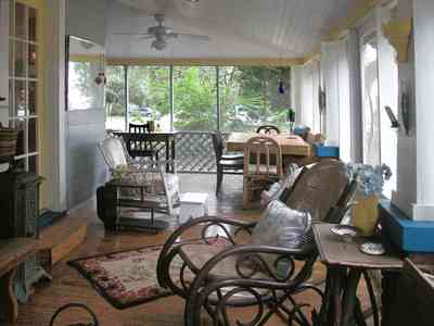 East-Pensacola-Heights:-600-Bayou-Blvd_04.jpg:  front porch, wicker furniture, ceiling fan, oriental rug, french door