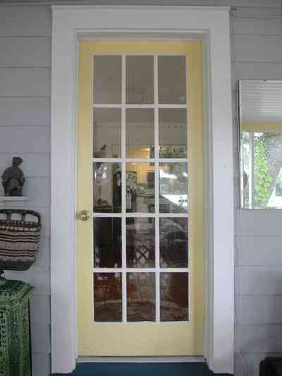 East-Pensacola-Heights:-600-Bayou-Blvd_06.jpg:  front door, front porch, french door, pine lap siding, wicker basket, bayou, cottage