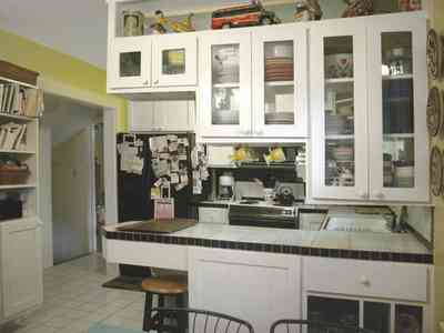 East-Pensacola-Heights:-600-Bayou-Blvd_12.jpg:  kitchen cabinets, glass cabinet doors, library, white ceramic tile floors, kitchen stool