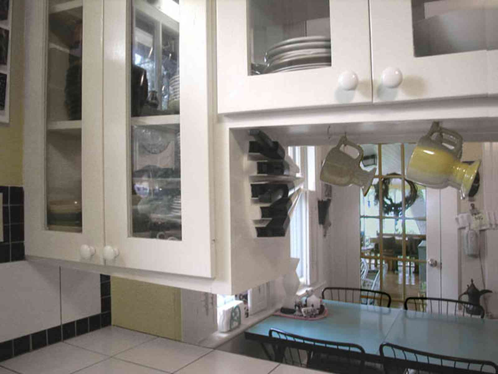 East-Pensacola-Heights:-600-Bayou-Blvd_15.jpg:  glass front cabinets, kitchen, dining area, hanging cups, ceramic tile countertops, screened porch