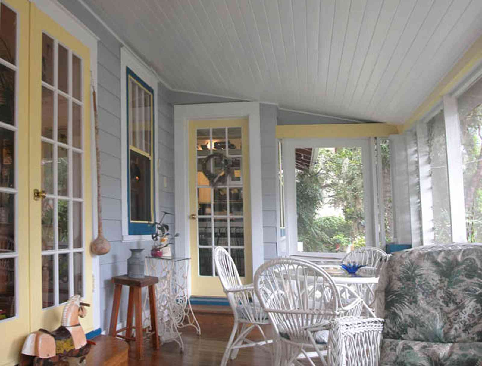 East-Pensacola-Heights:-600-Bayou-Blvd_24.jpg:  screened porch, wicker furniture, wooden floors, french doors