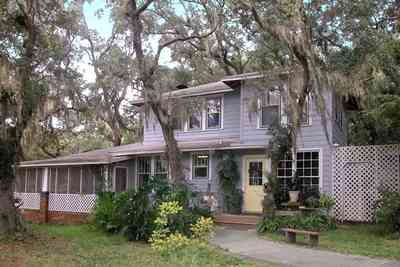 East-Pensacola-Heights:-600-Bayou-Blvd_26.jpg:  wood frame construction, mossy oaks, spanish moss, side door, screen porch, brick pillars, bayou view, camellia bush,