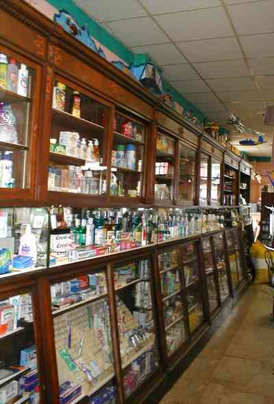 Foley:-Staceys-Drugstore_13.jpg:  drugstore, soda fountain, banana split, glass display cases, soda shop, awning, store front, brick building, art deco architecture, counter, cracker barrel, malts, milkshake, prescription drugs, druggist, card racks