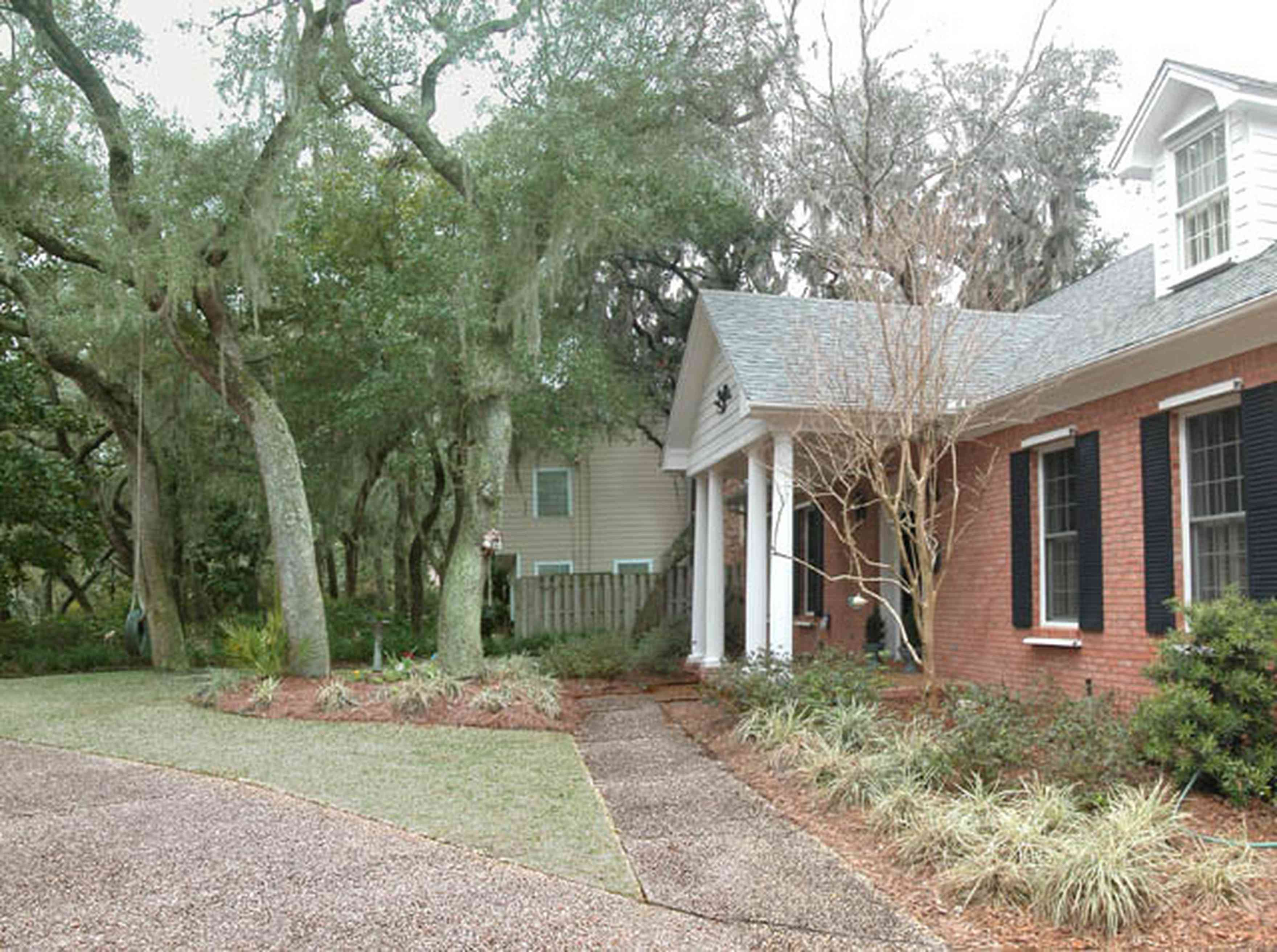 Gulf-Breeze:-228-North-Cliff-Dr_02.jpg:  colonial architectural style, columns, dormer window, shutters, oak trees, driveway, sidewalk, subdivision