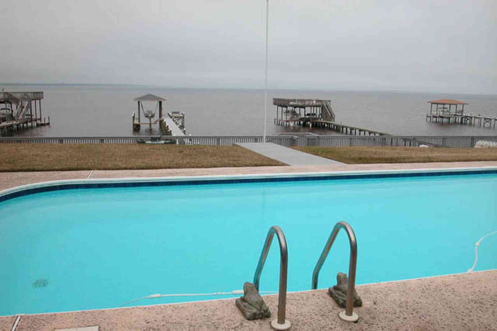 Gulf-Breeze:-228-North-Cliff-Dr_03.jpg:  swimming pool, bay, dock, pier, deck, flag pole, boat, bayfront