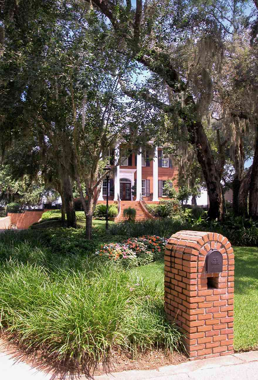 Gulf-Breeze:-506-Kenilworth-Drive_00.jpg:  red brick mansion, white columns, leaded glass door, mailbox, impatiens, brick wall, spanish moss, oak trees, shutters, porch