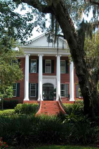 Gulf-Breeze:-506-Kenilworth-Drive_01.jpg:  red brick mansion, white columns, leaded glass door, mailbox, impatiens, brick wall, spanish moss, oak trees, staircase, wrought-iron bannisters, doric columns, pediment, shutters, porch