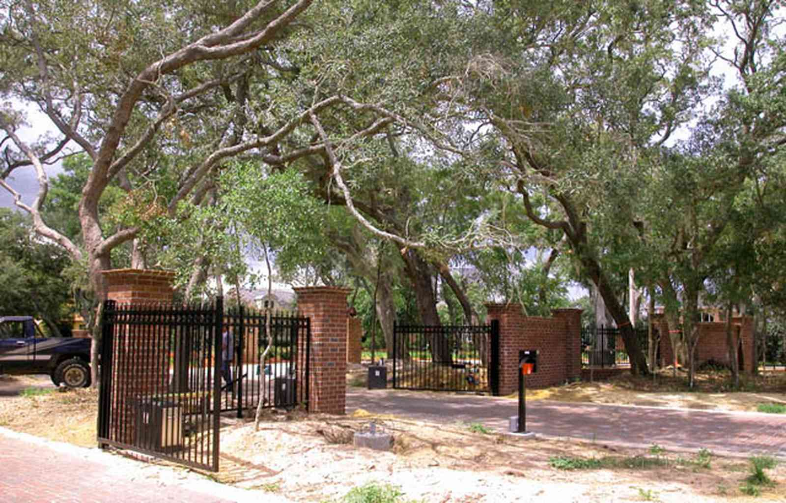 Gulf-Breeze:-706-Fair-Point-Drive_03.jpg:  gate, entrance, formal driveway, lanterns, oak trees, privacy gate, wrought-iron fence, brick columns