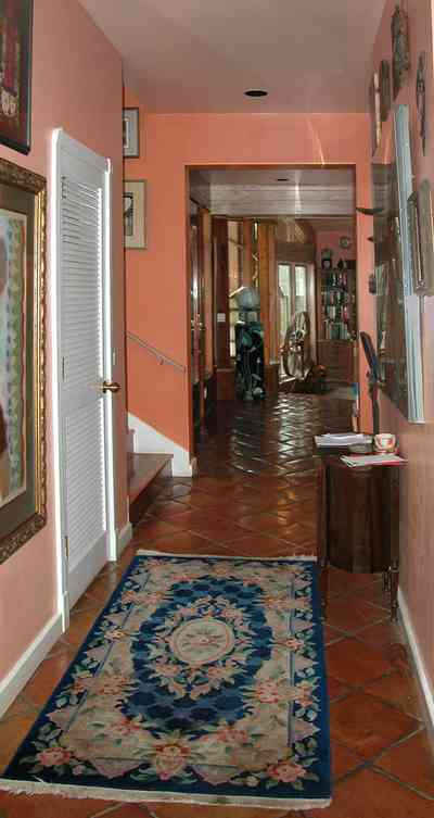 Gulf-Breeze:-92-High-Point-Drive_09.jpg:  hallway, stairs, credenza, oriental rug, spinning wheel, mexican tile floor