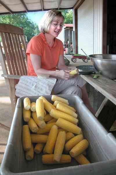 Hollandtown:-Holland-Farm:-Corn-Harvest_01.jpg:  corn cob, shuck corn, farmers wife, red wagon, barn, rocking chair