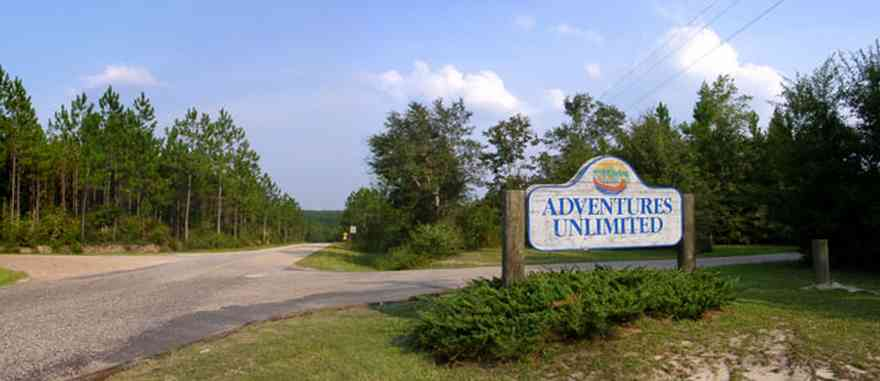 Milton:-Adventures-Unlimited_01.jpg:  sign, road, hwy 87, pine tree, santa rosa county