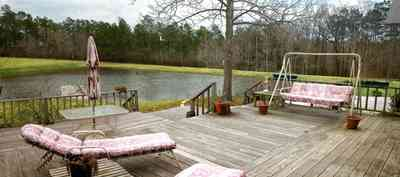 Milton:-Floyd-Farm_03.jpg:  porch, deck, fireplace, log cabin, hills, valley, pond, oak trees, sofa, chaise lounge, umbrella table, lake