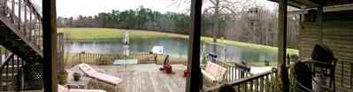 Milton:-Floyd-Farm_04a.jpg:  porch, deck, fireplace, log cabin, hills, valley, pond, oak trees, sofa, chaise lounge, umbrella table, lake