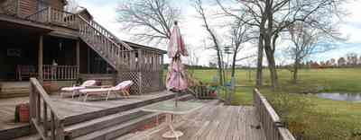 Milton:-Floyd-Farm_05a.jpg:  porch, deck, fireplace, log cabin, hills, valley, pond, oak trees, sofa, chaise lounge, umbrella table, lake