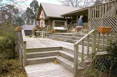 Milton:-Floyd-Farm_06.jpg:  porch, deck, fireplace, log cabin, hills, valley, pond, oak trees, sofa, chaise lounge, umbrella table, lake