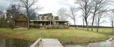 Milton:-Floyd-Farm_07.jpg:  porch, deck, fireplace, log cabin, hills, valley, pond, oak trees, sofa, chaise lounge, umbrella table, lake