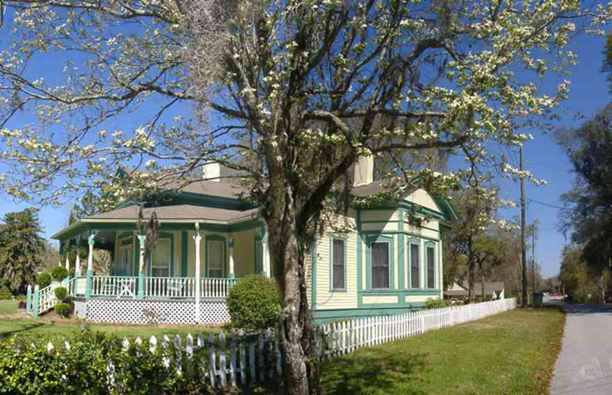 Milton:-Historic-District:-202-Berryhill-Street:-Chadwick-Hartsell-House_03.jpg:  dogwood tree, picket fence, steamboat house, porch, shutters, wooden