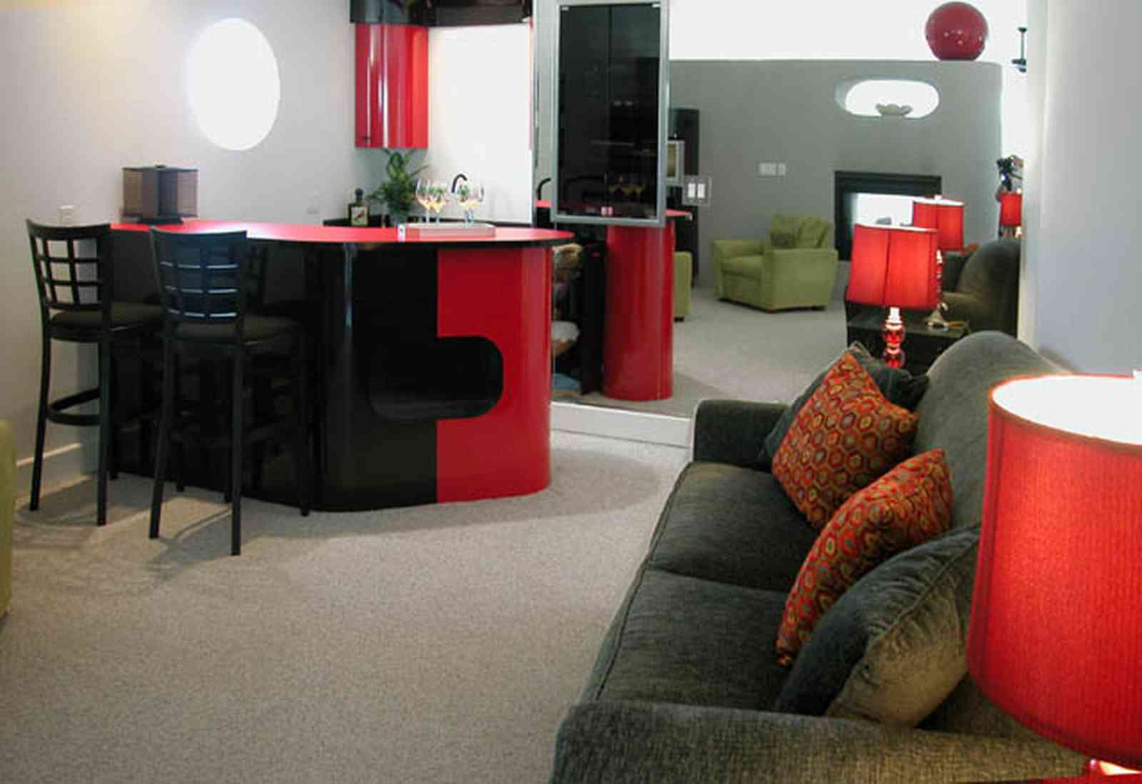 Navarre:-7332-Grand-Navarre-Blvd_26.jpg:  brown suede sofa, red jewel lamps, black laquer cabinets, bar, mirrored wall, round windows, white carpet