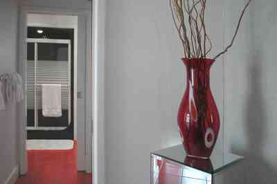 Navarre:-7332-Grand-Navarre-Blvd_30.jpg:  red glass vase, red tile floor, black shower door, art deco decor, mirrored stand