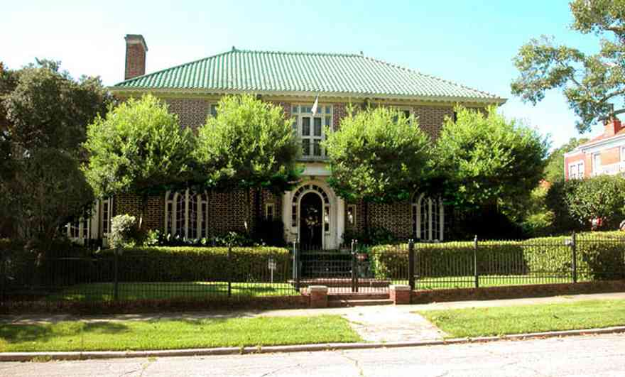 North-Hill:-105-West-Gonzales-Street_01.jpg:  red brick house, fireplace, sidewalk, wrought iron fence, green tile roof