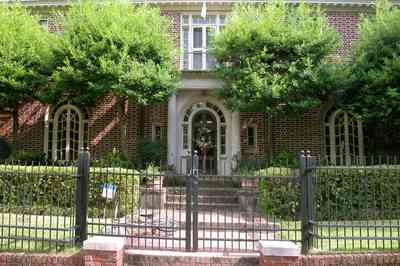 North-Hill:-105-West-Gonzales-Street_02.jpg:  red brick house, fireplace, sidewalk, wrought iron fence, green tile roof