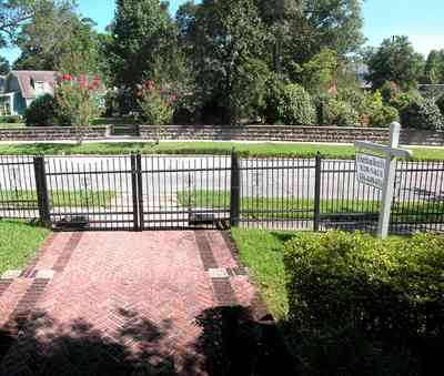 North-Hill:-105-West-Gonzales-Street_02b.jpg:  wrought-iron fence, herringbone brick sidewalk, red brick house, streetscape, crepe myrtle trees, stone wall