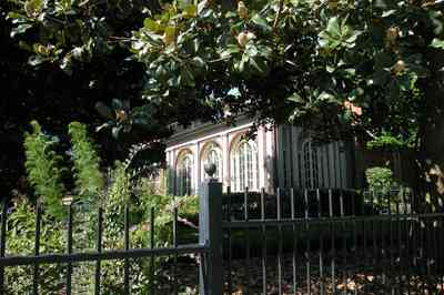 North-Hill:-105-West-Gonzales-Street_04.jpg:  wrought-iron fence, leaded glass windows, magnolia tree, french colonial architecture