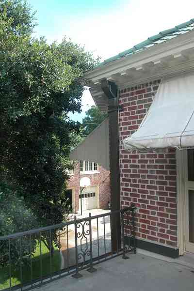 North-Hill:-105-West-Gonzales-Street_20a.jpg:  awning, balcony, side porch, wrought iron railing, oak tree, french colonial architecture, carriage house, basketball goal