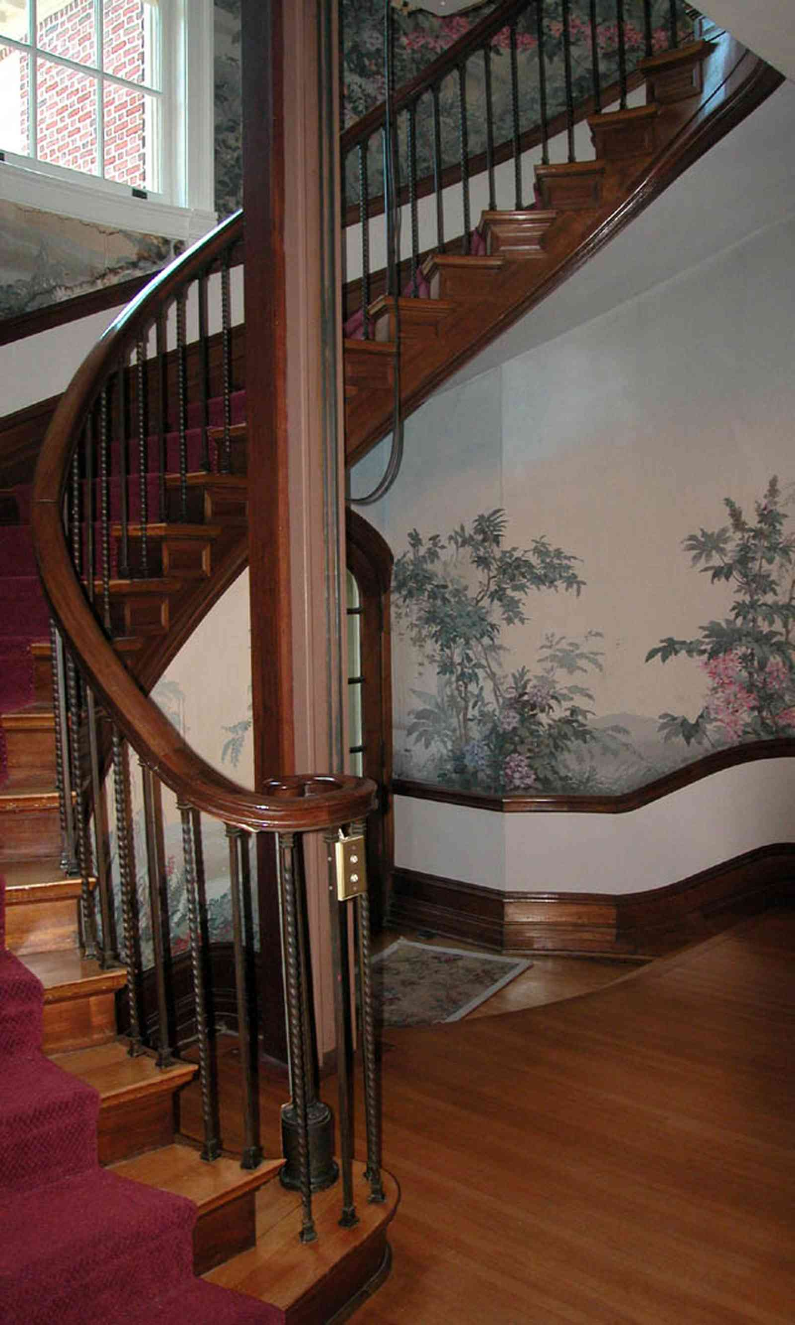 North-Hill:-105-West-Gonzales-Street_29.jpg:  grand foyer, oriental rug, spiral staircase, chandelier, hardwood floors, french colonial architecture, handpainted wallpaper