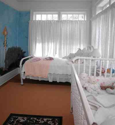 North-Hill:-105-West-Gonzales-Street_65.jpg:  baby crib, stuffed animals, white eyelet curtains, quilt, wall mural