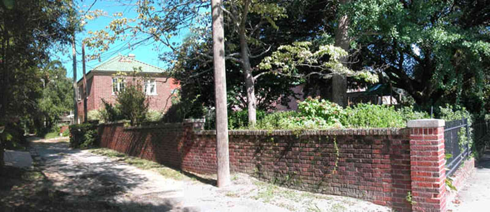 North-Hill:-105-West-Gonzales-Street_70.jpg:  service alley, brick fence, retaining wall, telephone lines, carriage house, garage, oak tree