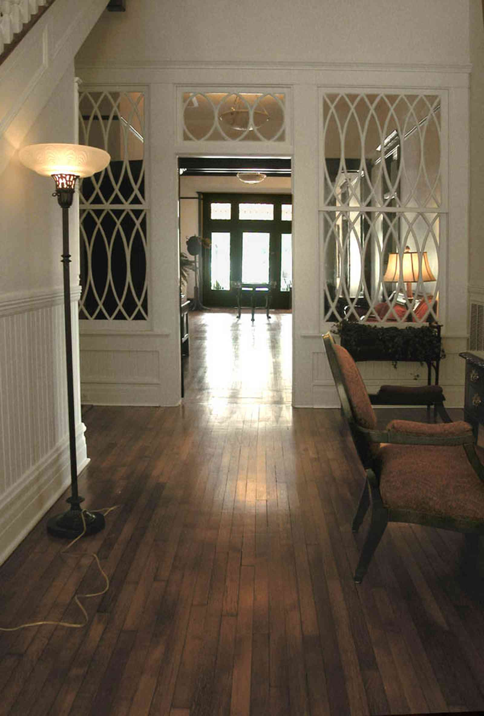 North-Hill:-116-DeSoto-St_02f.jpg:  central hall, heartpine floors, transom, red brocade chair, desk, floor lamp, staircase