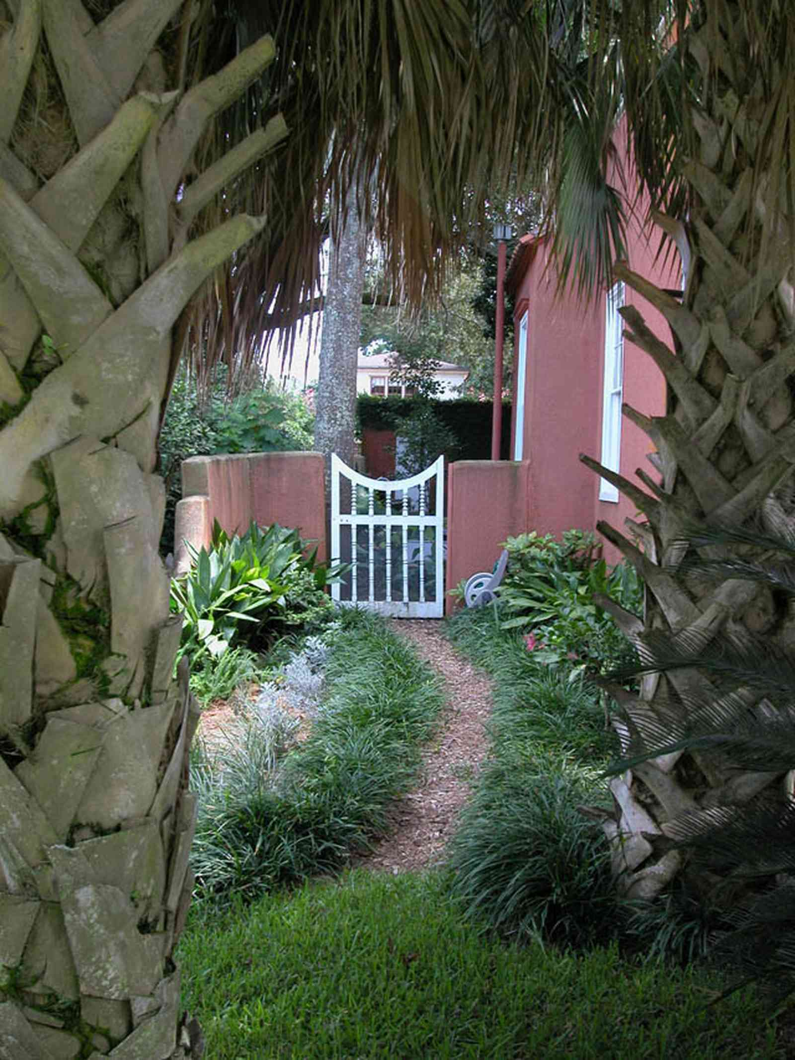 North-Hill:-123-West-Lloyd-Street_02.jpg:  palm trees, gate, garden, gravel path, stucco house, walled garden, north hill preservation district