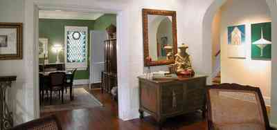 North-Hill:-123-West-Lloyd-Street_10.jpg:  living room, arched doorway, oriental rug, stained glass window, wicker chair
