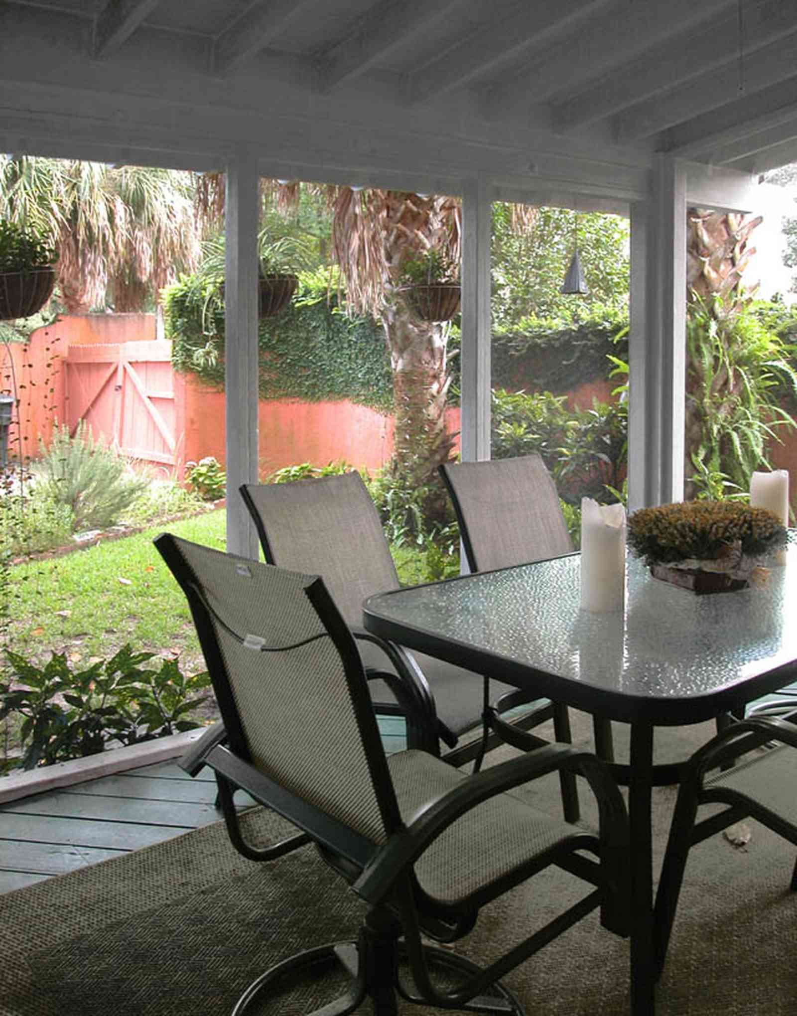 North-Hill:-123-West-Lloyd-Street_25.jpg:  screened porch, stucco walls, vine covered wall, garden gate, garden, backyard, palm trees, glass-top table