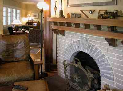 North-Hill:-284-West-Gonzales-Street_16.jpg:  leather chair, stone fireplace, fire screen, wooden mantle, craftsman cottage