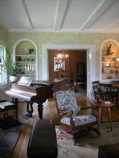 North-Hill:-284-West-Gonzales-Street_17.jpg:  rocking chair, card table, baby grand piano, candleabra, footstool, crewel rug, mother-in-law\