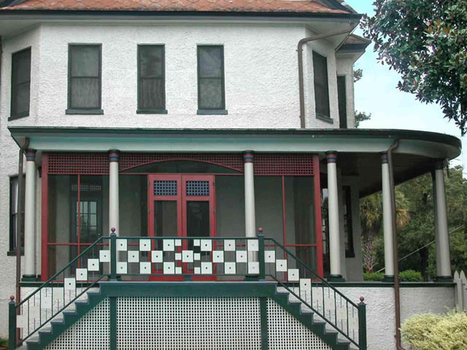 North-Hill:-304-West-Gadsden-Street_26.jpg:  side porch, column, stairs, stucco house, magnolia tree, lattice work