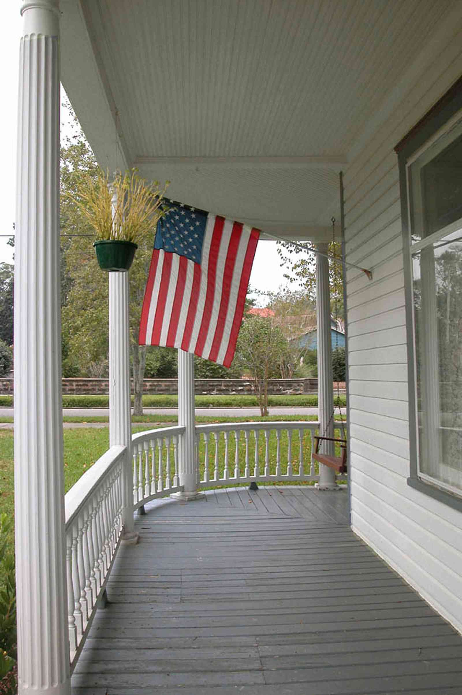 North-Hill:-52-West-Gonzalez-Street_04.jpg:  victorian front porch, queen anne style, american flag, curved railing