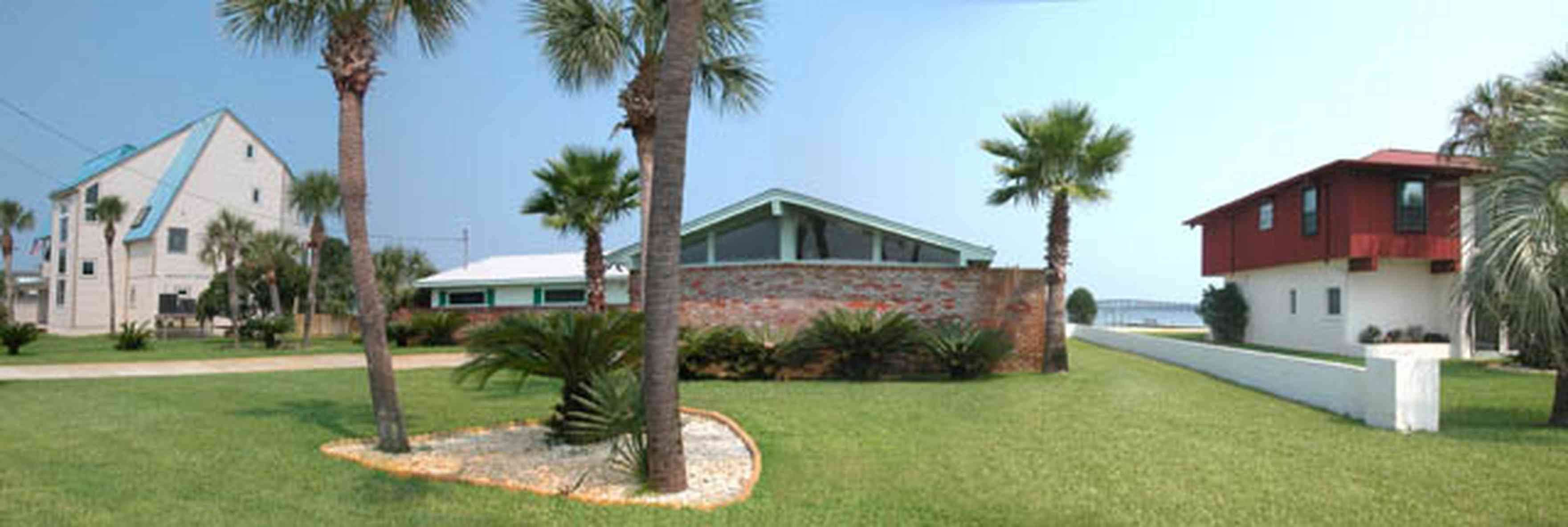 Pensacola-Beach:-231-Sabine-Drive_01.jpg:  palm trees, 1950's architecture, brick house, pensacola bay, soundside